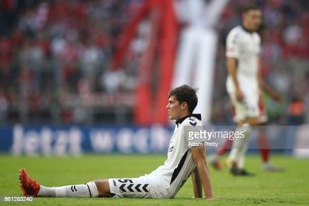 Pascal Stenzel of Freiburg sits dejected on the pitch after the Bundesliga match between FC Bayern Muenchen and SportClub Freiburg at Allianz Arena...