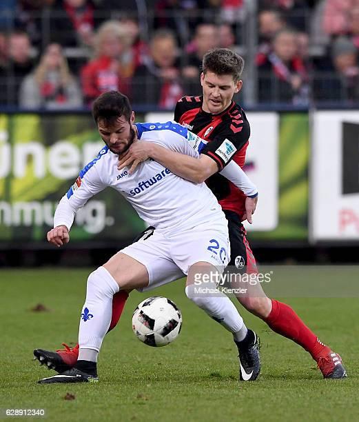 Pascal Stenzel of SC Freiburg challenges Marcel Heller of SV Darmstadt 98 during the Bundesliga match between Sport Club Freiburg and SV Darmstadt 98...