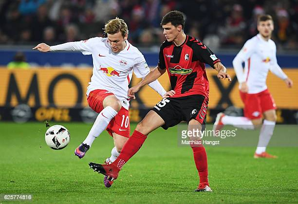Pascal Stenzel of SC Freiburg is challenged by Emil Forsberg of RB Leipzig during the Bundesliga match between SC Freiburg and RB Leipzig at...