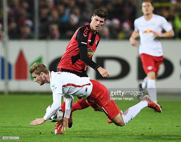 Pascal Stenzel of SC Freiburg tackles Timo Werner of RB Leipzig during the Bundesliga match between SC Freiburg and RB Leipzig at SchwarzwaldStadion...