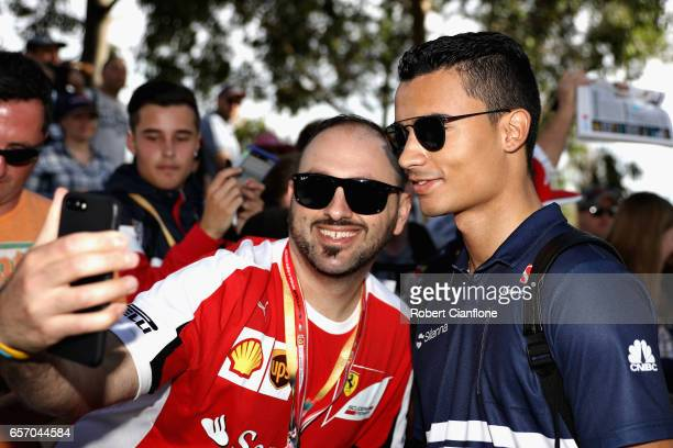 Pascal Wehrlein of Germany and Sauber F1 arrives at the circuit and poses for a photo with a fan during practice for the Australian Formula One Grand...