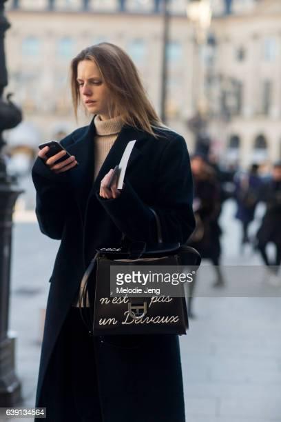 Pascaline Smets checks her phone wears Vetements and a Delvaux bag outside the Balenciaga show at Place Vendome on January 18 2017 in Paris France