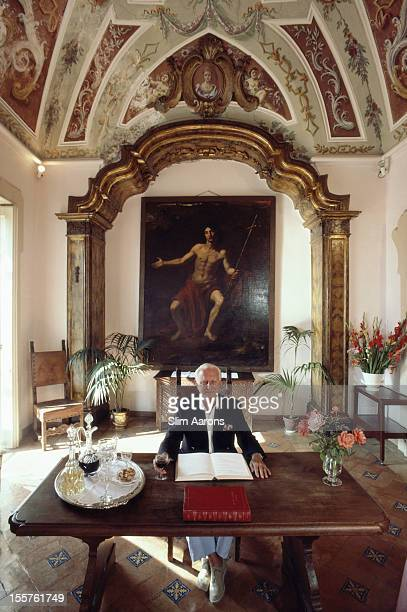 Pascuale Vuilleumier poses with an open book and a glass of red wine on the table before him in front of a painting by Caravaggio at his hotel Villa...