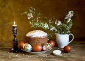 Paska (traditional Ukrainian Easter cake) and Easter eggs on a plate, beside burning candle and blooming cherry branches
