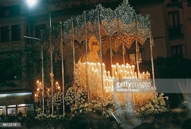 A paso or float surmounted with an effigy of the Virgin Mary during Semana Santa or Holy Week in Spain probably Seville circa 1960 The float is...