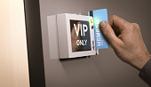 Hand with blue pass card unlocking access to a VIP room. Concept image for illustration of customers exclusive privileges.