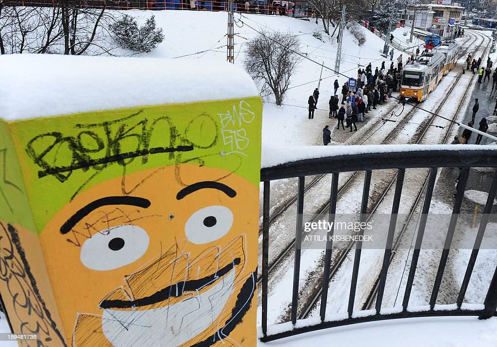 Passangers stand at the snow-covered tram station in Budapest, 12th district on January 14, 2013 as the Hungarian capital and several counties are hit by about 20 cm snow last night and this morning. The heavy snowfalls caused chaos in traffic and public transport. AFP PHOTO / ATTILA KISBENEDEK