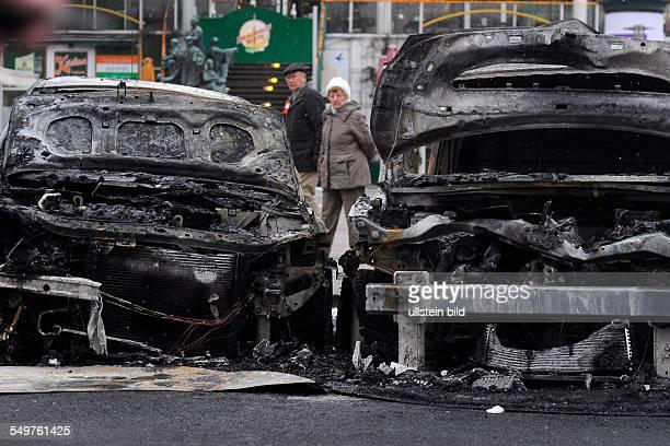 Passanten betrachten die ausgebrannten Wracks von zwei Autos in BerlinMitte Sie wurden in der Nacht zuvor von Unbekannten angezündet und durch das...