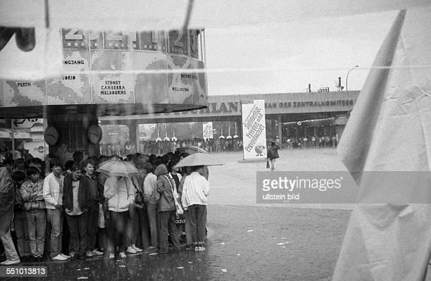 Passanten flüchten vor einem Regenguss unter die Weltzeituhr auf dem Ostberliner Alexanderplatz am Rande des Pfingsttreffen der FDJ in OstBerlin
