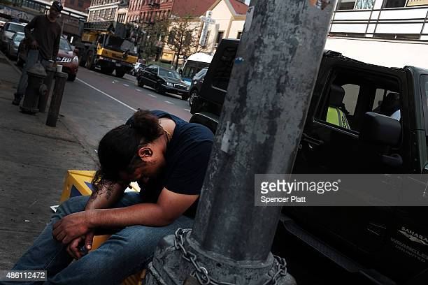 A passed out man sits along a sidewalk in an area which has witnessed an explosion in the use of K2 or 'Spice' a synthetic marijuana drug in East...
