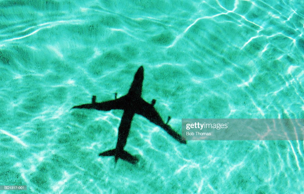 Passenger aircraft casting shadow on water (cross-processed) : Stock Photo