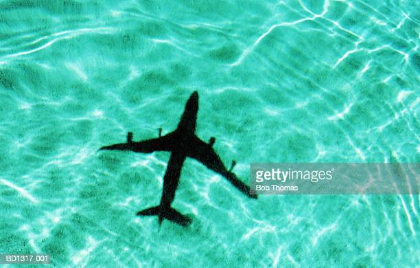 Passenger aircraft casting shadow on water (cross-processed)