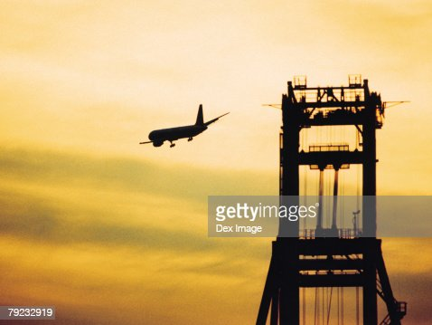 Passenger aircraft flying over port at sunset : Stock Photo