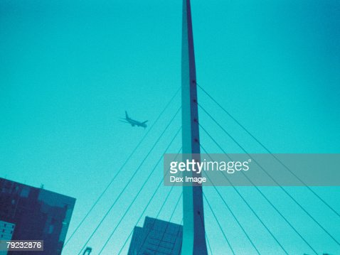 Passenger aircraft flying over skyscraper : Stock Photo