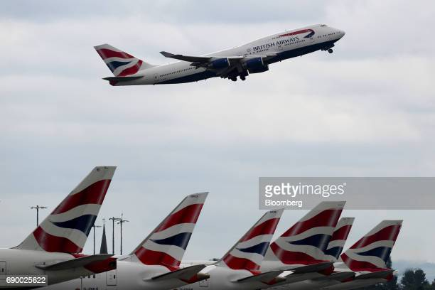 A passenger aircraft operated by British Airways a unit of International Consolidated Airlines Group SA takes off over tail fins on British Airways...