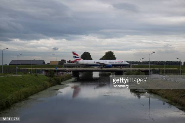 A passenger aircraft operated by British Airways a unit of International Consolidated Airlines Group SA crosses a bridge after landing at Schiphol...
