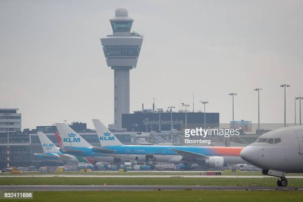 Passenger aircraft operated by KLM the Dutch arm of Air FranceKLM Group stand at boarding gates at Schiphol airport in Amsterdam Netherlands on...