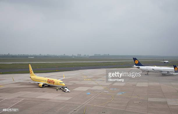 A passenger aircraft operated by lowcost airline TUI Fly is towed on the tarmac as aircraft operated by Deutsche Lufthansa AG stand beyond at...