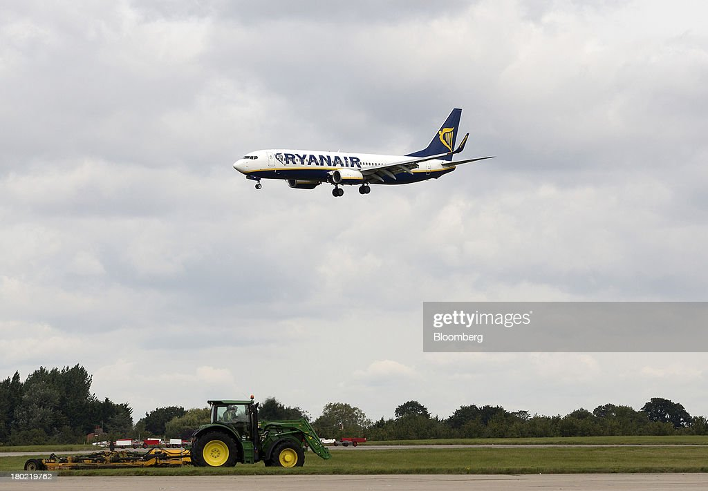 A passenger aircraft operated by Ryanair Holdings Plc comes into land as a maintenance tractor moves along the grass at Stansted Airport, operated by Manchester Airports Group (MAG) in Stansted, U.K., on Tuesday, Sept. 10, 2013. From two planes in 1995, EasyJet has grown to more than 200 Airbus SAS aircraft carrying more than 59 million people annually, 20 million fewer than Ryanair. Photographer: Simon Dawson/Bloomberg via Getty Images