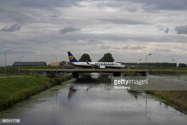 A passenger aircraft operated by Ryanair Holdings Plc crosses a bridge after landing at Schiphol airport in Amsterdam Netherlands on Tuesday Aug 15...