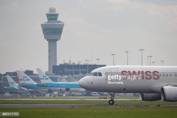 A passenger aircraft operated by Swiss International Air Lines Ltd taxis as KLM jets operated by the Dutch arm of Air FranceKLM Group stand beyond at...