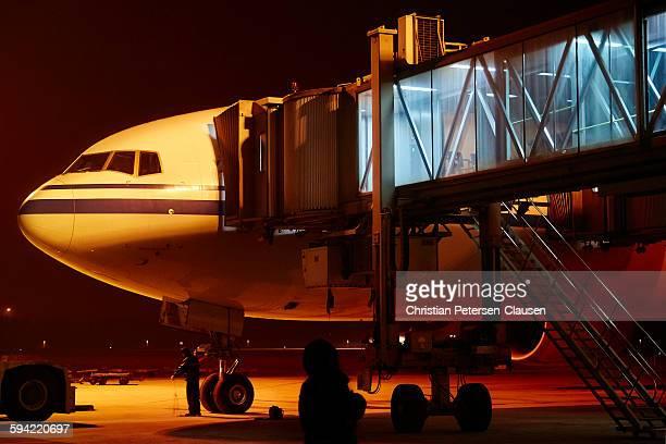 Passenger airplane at airport terminal at night