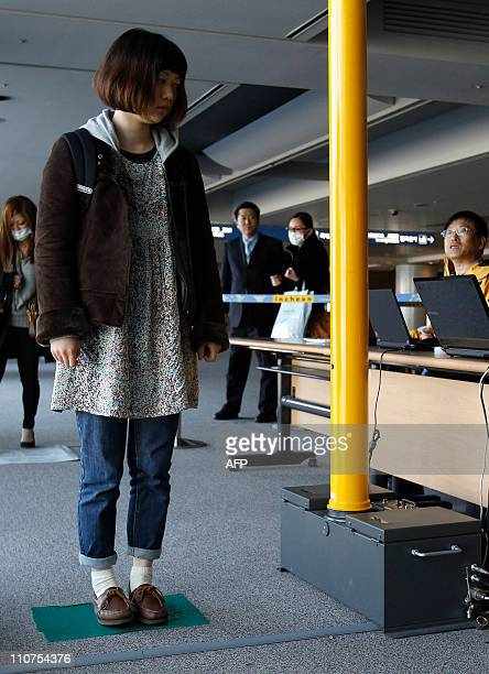 A passenger arriving from Japan passes through a scanner to check radiation levels at Incheon international airport west of Seoul on March 17 2011...