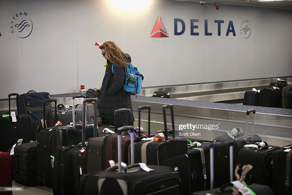 A passenger at O'Hare International Airport searches for her luggage on December 21, 2012 in Chicago, Illinois. Today is the busiest air travel day of the Christmas holiday, with an estimated 200,000 travelers expected to travel through O'Hare today.