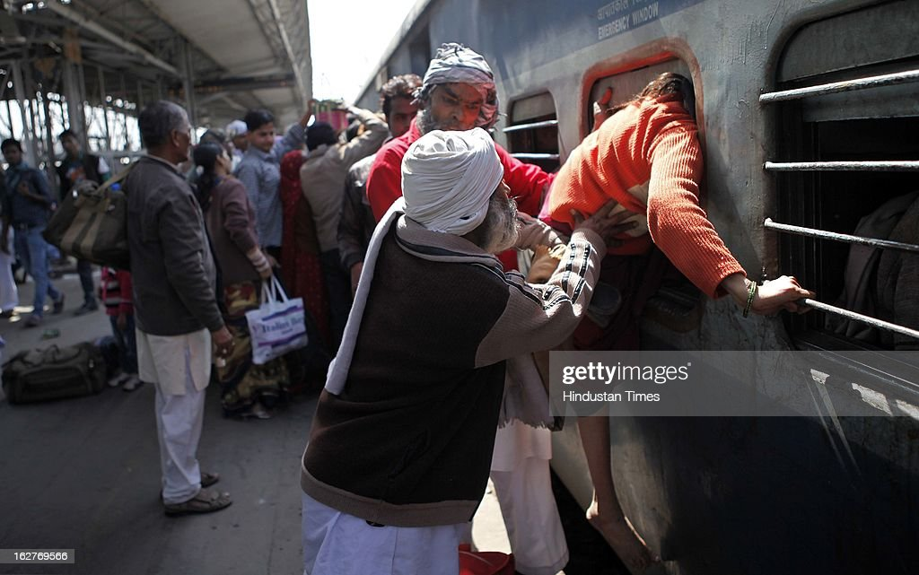 Passenger boarding a train through an emergency window at Nizamuddin railway station on February 26, 2013 in New Delhi, India. Indian Railway Minister Pawan Kumar Bansal presented his maiden Railway budget for the next fiscal year in the parliament.