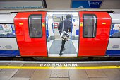 Passenger boarding London Underground Train at Tooting Bec station Text says 'mind the gap'