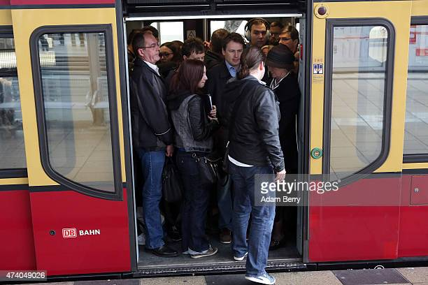 A passenger boards a crowded regional SBahn train at Alexanderplatz train station during a train strike on May 20 2015 in Berlin Germany German rail...