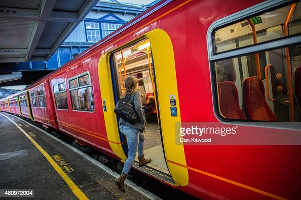 A passenger boards a train at Clapham Junction on January 2 2015 in London England Increased rail fares averaging 25% come into effect today pushing...