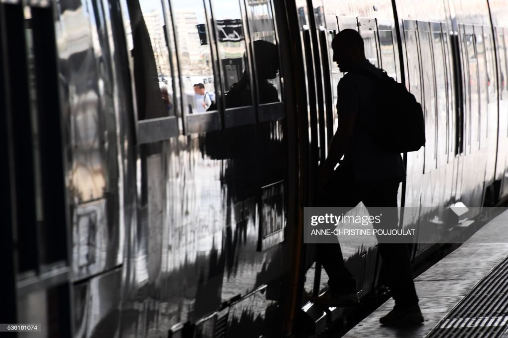 A passenger boards a train in the Saint-Charles rail station in Marseille, southeastern France, on May 31, 2016, at the start of a strike by employees of French state-owned rail operator SNCF to protest against government labour reforms. France is bracing for a week of severe disruption to transport after unions called for more action in their bitter standoff with the Socialist government over its labour market reforms. / AFP / ANNE
