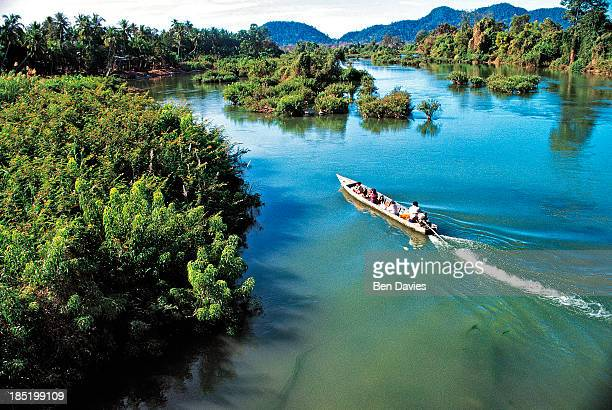 A passenger boat navigates along the Mekong River near Don Det in Southern Laos This region is known as Si Phan Don or Four Thousand Islands after...