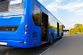 the blue bus is approaching the bus stop to pick up passengers