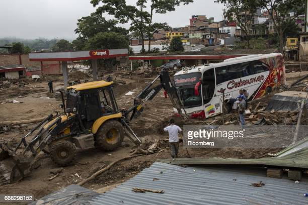 A passenger bus is pulled from debris at a destroyed Organizacion Terpel SA gas station after a landslide in Mocoa Putumayo Colombia on Monday April...