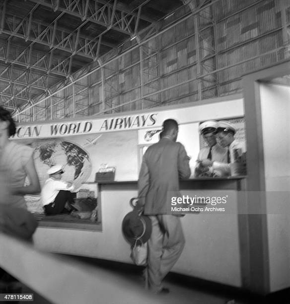 A passenger buys a ticket at the Pan American Airways counter at the airport circa 1947 in San Juan Puerto Rico