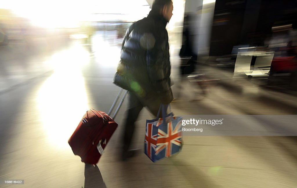 A passenger carries a Union Jack-branded bag as he wheels his luggage through the check-in area of the north terminal at Gatwick airport in Crawley, U.K., on Friday, Dec. 21, 2012. U.K. airports predicted today to be the busiest day during the Christmas period, as some Britons opt to spend the holidays abroad and overseas visitors fly out to be with friends and family. Photographer: Chris Ratcliffe/Bloomberg via Getty Images