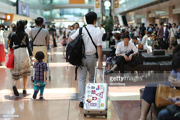 A passenger carries his suitcase as he walks through the departure lobby at Haneda Airport in Tokyo Japan on Wednesday Aug 12 2015 Treasuries'...