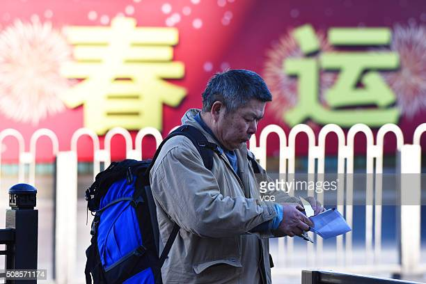 A passenger carrying luggage walks toward Beijing West Railway Station as he heads back home for the upcoming Spring Festival on February 5 2016 in...