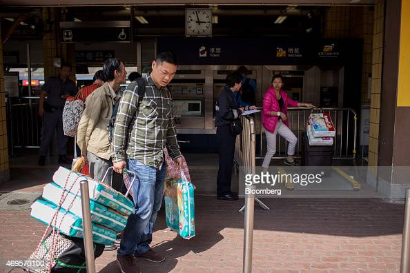 A passenger center holding a shopping cart laden with baby diapers stands in line as another passenger right has her luggage weighed and inspected by...
