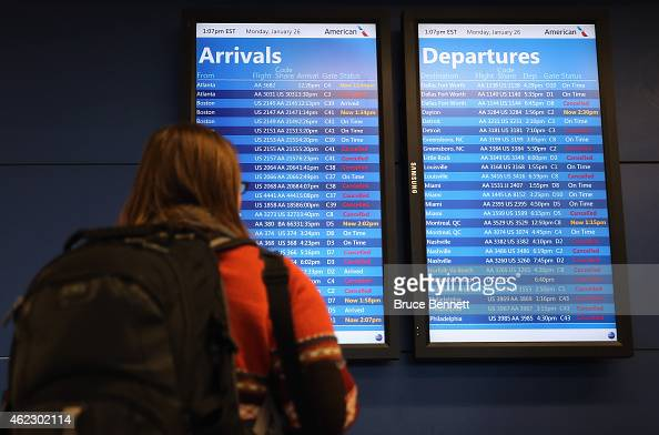 A passenger checks for flight status at Laguardia Airport on January 26 2015 in New York City Much of the Northeast is bracing for a major winter...