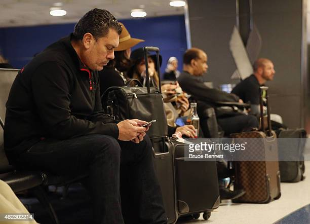 A passenger checks his cell phone as storm conditions worsen at Laguardia Airport on January 26 2015 in New York City Much of the Northeast is...