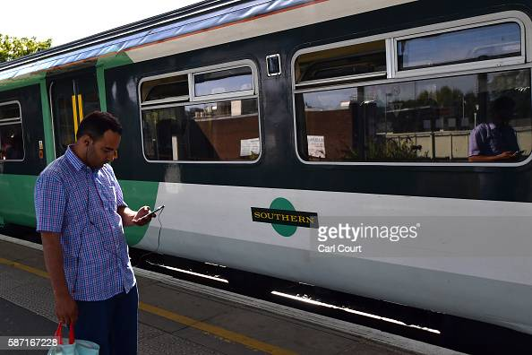 A passenger checks his phone on a platform as a train operated by Southern passes at Peckham Rye station on August 8 2016 in London England Hundreds...