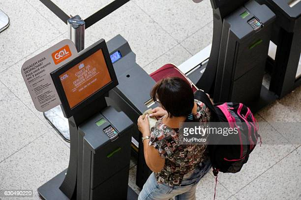 Passenger checks in a selfservice machine in the lobby of Santos Dumont Airport in Rio de Janeiro Brazil on 23 December 2016 With the festivities of...