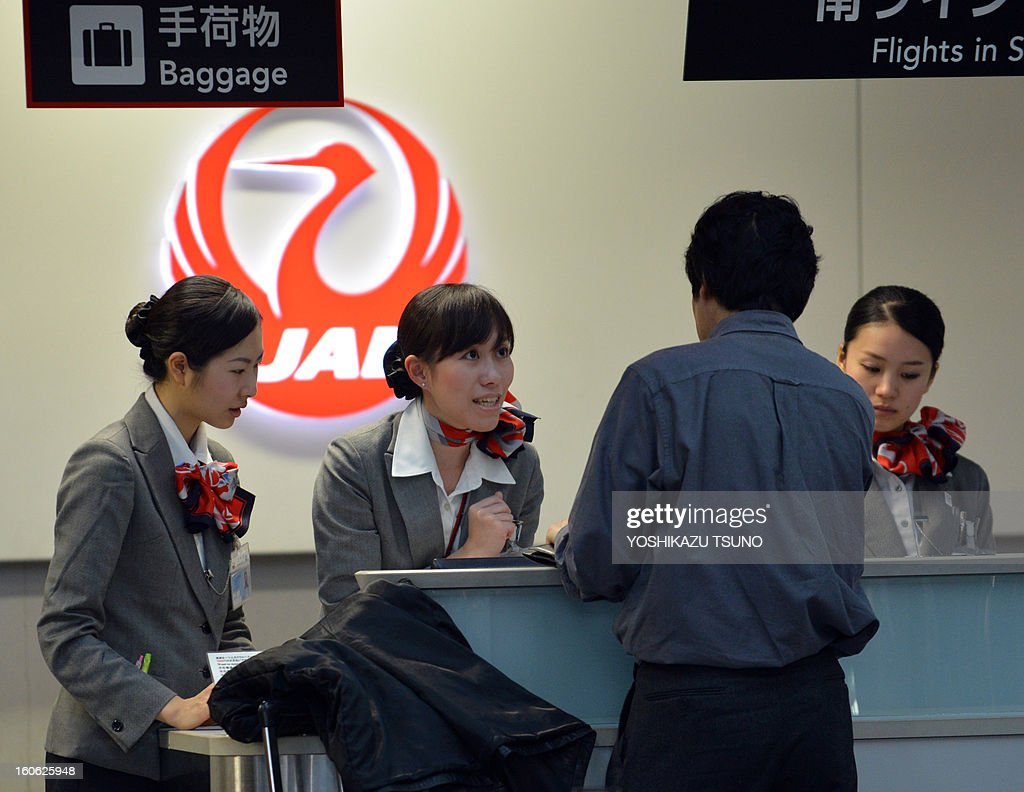 A passenger checks in at a Japan Airlines (JAL) counter at Tokyo's Haneda airport on February 4, 2013. JAL said that its net profit in the nine months to December slipped 3.7 percent to 1.52 billion USD, but the carrier boosted its full-year profit estimate. JAL and rival All Nippon Airways (ANA) have been hit by the worldwide grounding of Boeing's Dreamliner following an emergency landing by an ANA domestic flight earlier this month. AFP PHOTO / Yoshikazu TSUNO