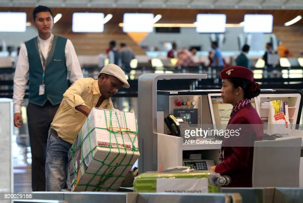 A passenger checksin for a Qatar Airways flight at the Hamad International Airport in Doha on July 20 2017 / AFP PHOTO / STRINGER