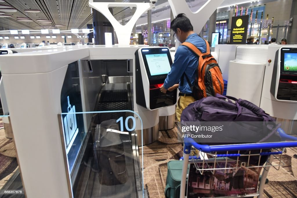 A passenger checks-in his luggage using an automated booth at the newly-opened Changi International Airport's Terminal 4 in Singapore on October 31, 2017. Singapore's newly-opened automated Changi International airport Terminal 4 began full operations on October 31. The cutting edge terminal, which is half the size of Terminal 3 at 225,000 square meters, makes it Changi Airport's smallest terminal. /