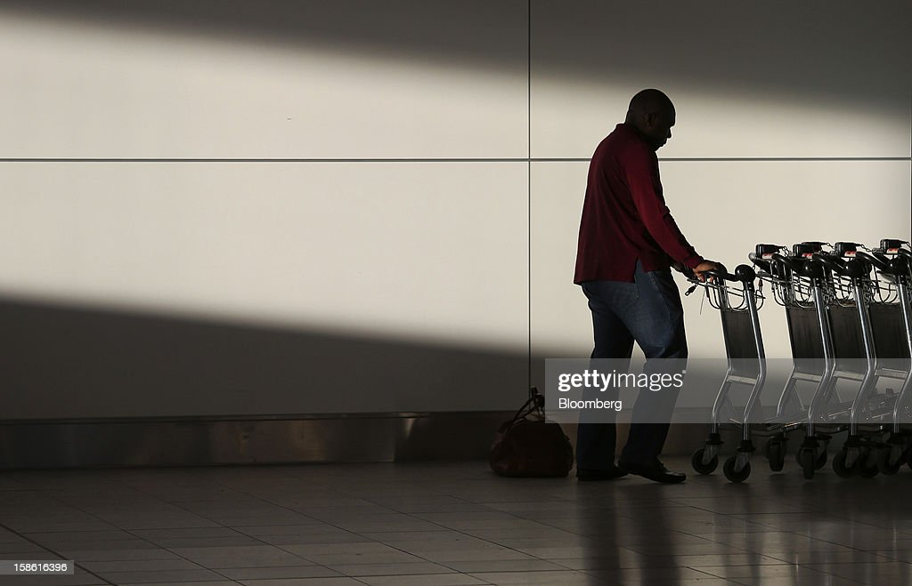 A passenger collects a luggage trolley in the north terminal at Gatwick airport in Crawley, U.K., on Friday, Dec. 21, 2012. U.K. airports predicted today to be the busiest day during the Christmas period, as some Britons opt to spend the holidays abroad and overseas visitors fly out to be with friends and family. Photographer: Chris Ratcliffe/Bloomberg via Getty Images
