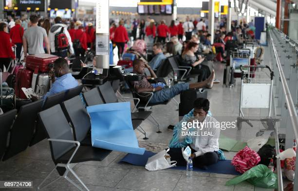 A passenger directly affected by a global computer crash that disrupted British Airways flights rests on the floor of Terminal 5 of London's Heathrow...